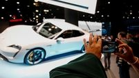 A visitor takes a picture of a Porsche Taycan electric car at the 2019 Frankfurt auto show.