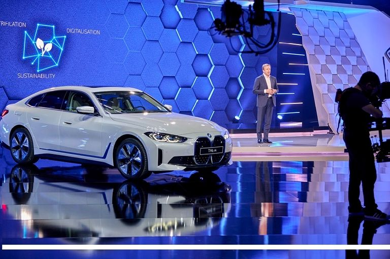 BMW CEO Oliver Zipse with the i4 electric sedan at the automaker's annual press conference on March 18