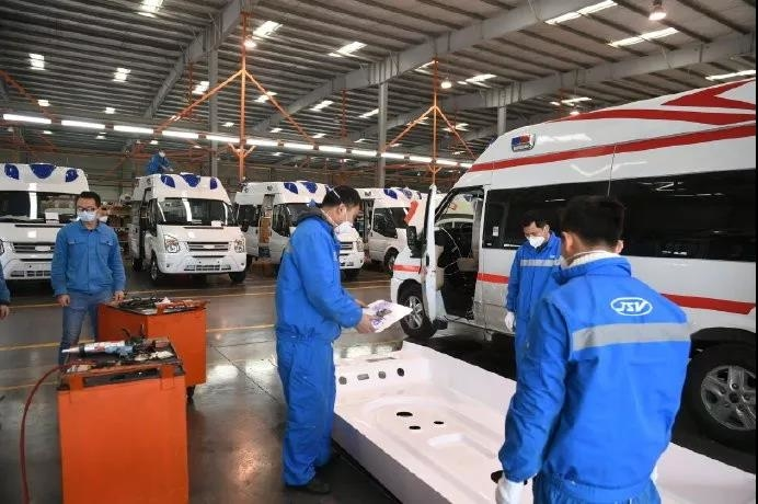 Ford workers modify transit vans.jpg
