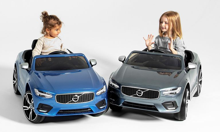 Two toddlers in Volvo toy cars