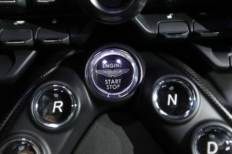 Aston Martinb logo on the botton used to start and stop the car's engine