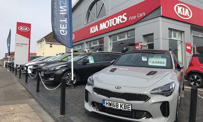 A Kia dealership in the UK. Showrooms are closed but customers can visit to pick up new cars ordered online.